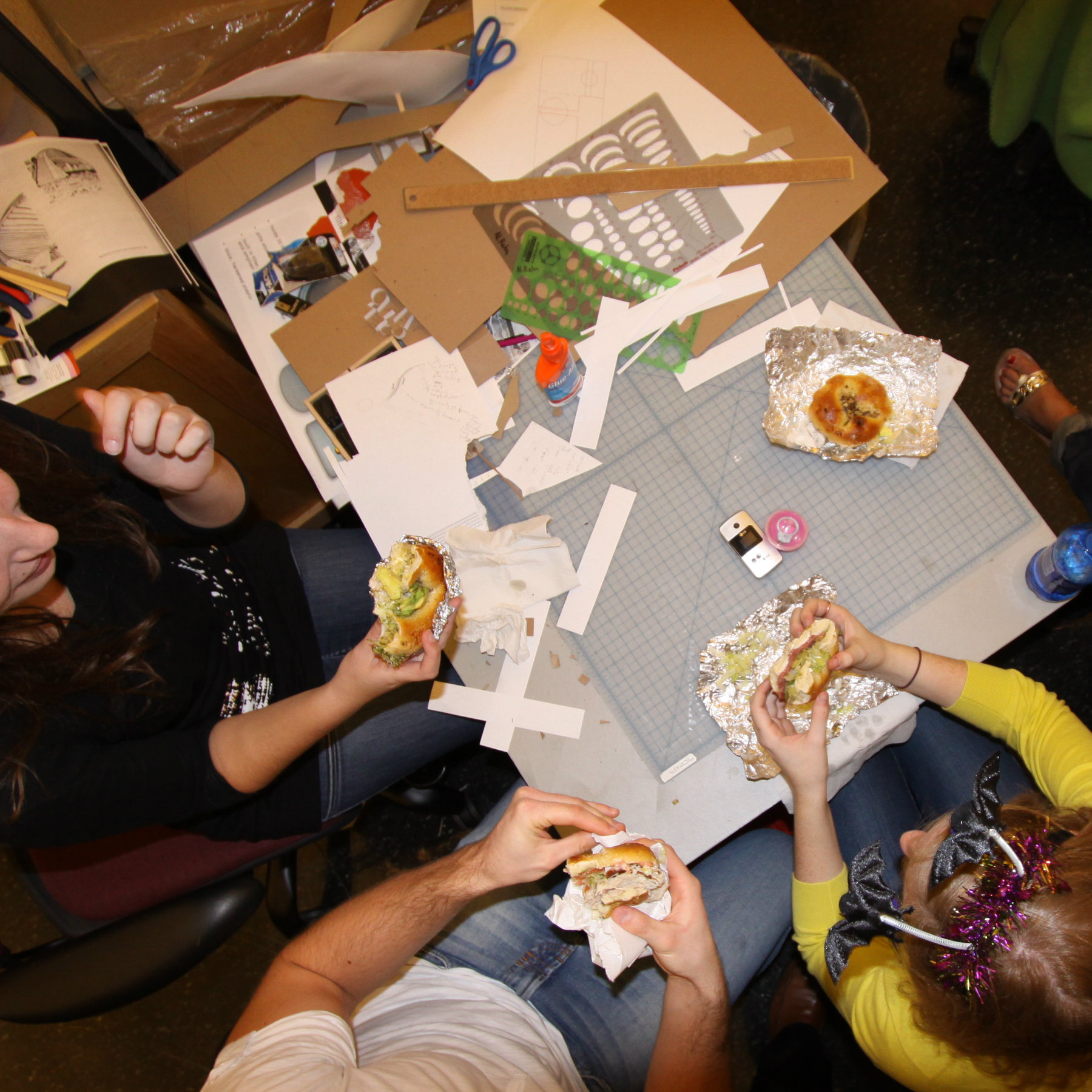 overhead view of students in studio eating bagel sandwiches