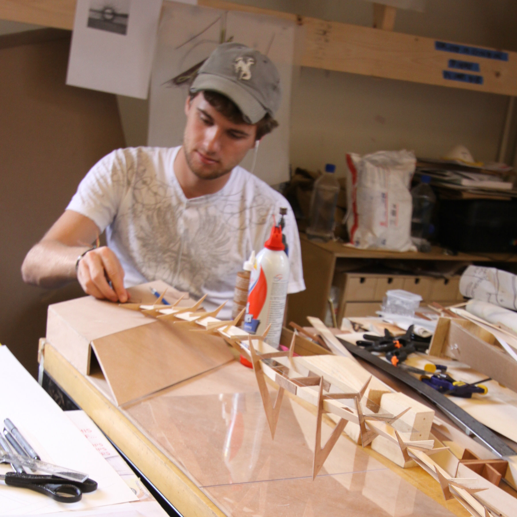male student glueing a wooden model