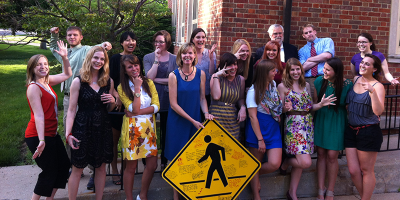 AIGA communication design students and faculty strike comical poses around an autographed crosswalk sign