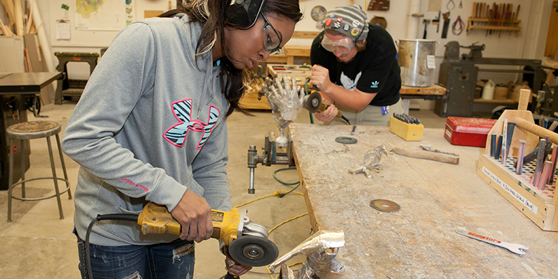 A student wearing ear and eye protection works with power tool to shape a metallic piece