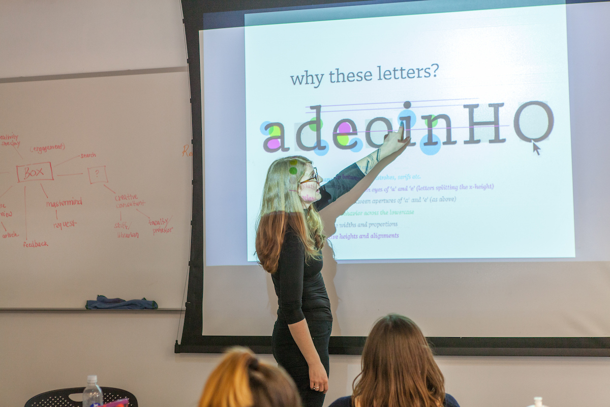 A visiting lecturer gestures to a PowerPoint slide about letterforms