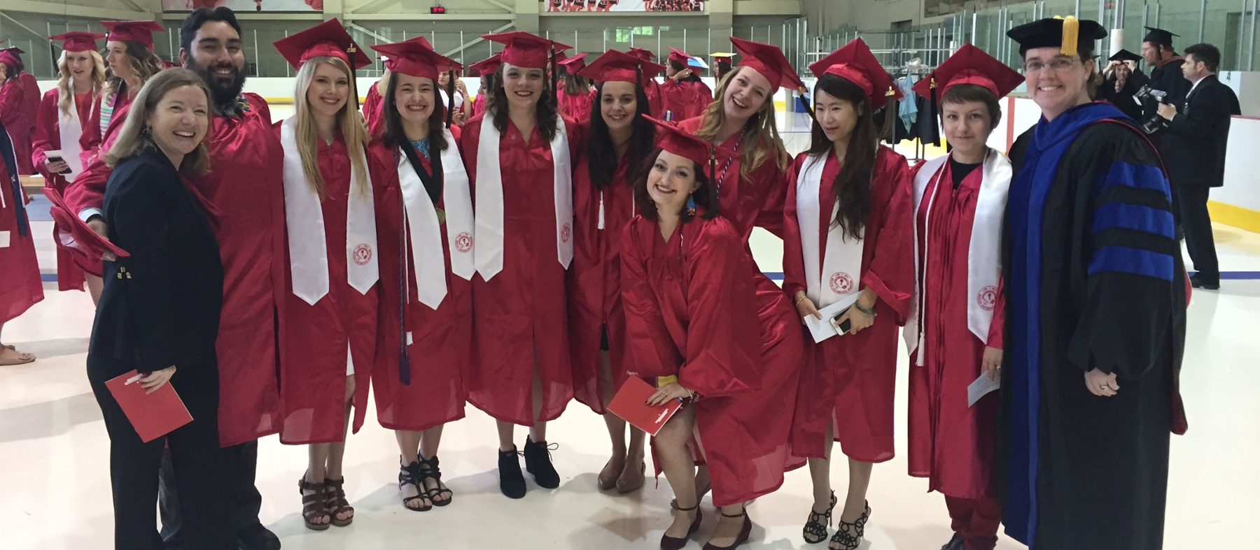 Recent art education graduates pose at Goggin Ice Arena