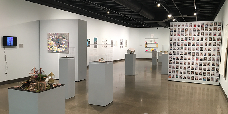 A view of Hiestand Galleries showing multimedia exhibits and a wall covered with snapshot sized photos