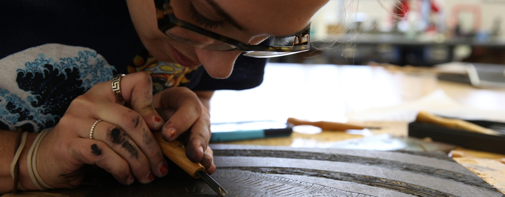 A printmaking student leans in close to work on a piece