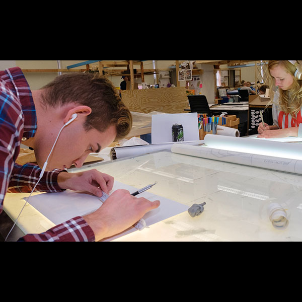 Two architecture students work opposite each other on projects on drafting boards