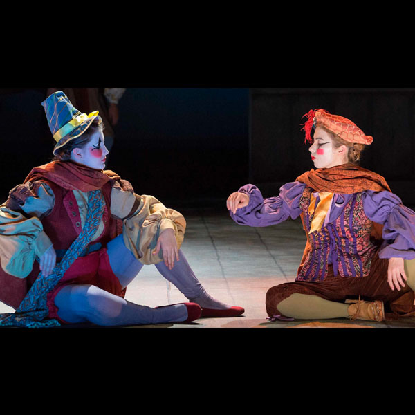 Two brightly colored harlequin characters in a scene from the Theatre Department production of Rosencrantz and Guildenstern are Dead