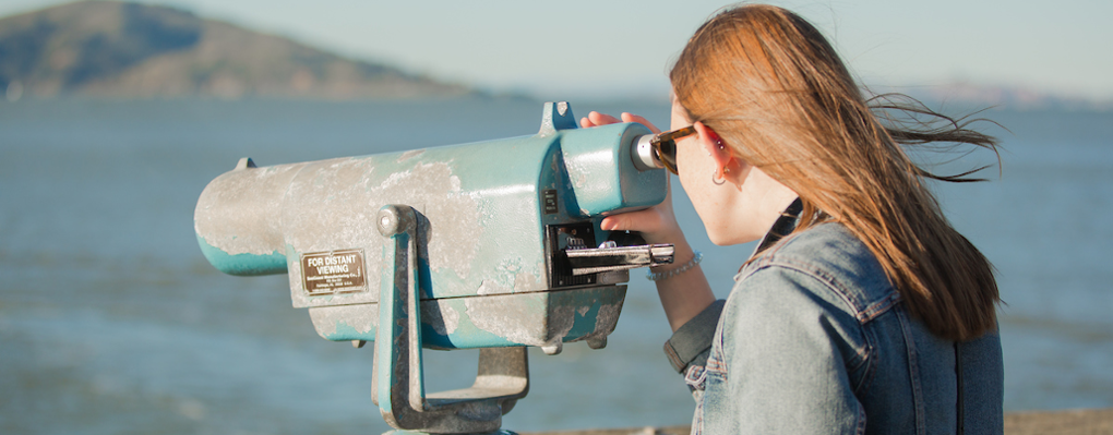 A woman uses a commercial binoculars viewer to look out over the ocean