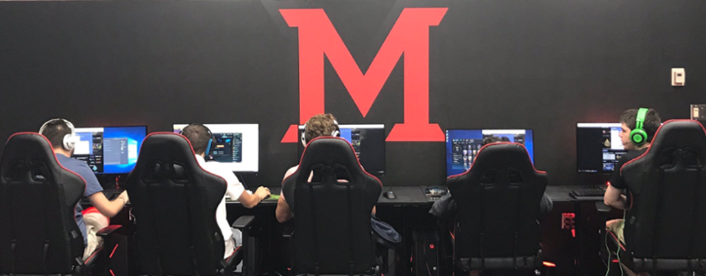 A row of students play video games, their backs to the viewer. On the wall, a large M.