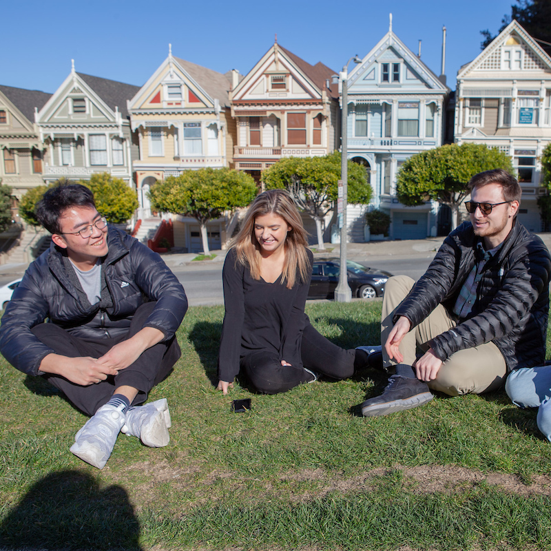 Students relax near a row of painted ladies houses in San Francisco
