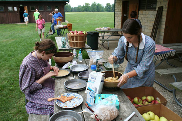 Women dressed in pioneer clothing make apple butter at a museum event