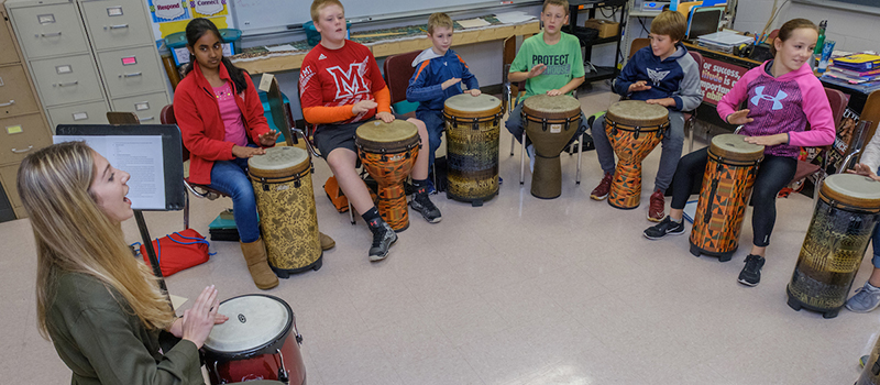 A student teacher leads her class in a percussion performance