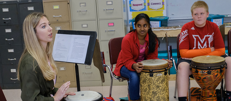 A student teacher leads her students in a drumming lesson