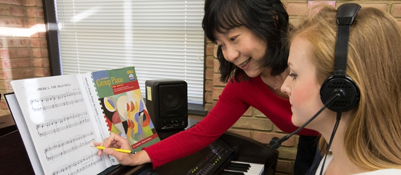 Dr. Tan works with a student wearing headphones who is participating in group piano class