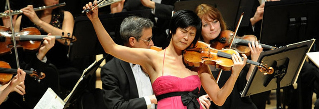 An elegantly attired violin soloist sweeps the bow high off the strings while the orchestra plays behind her