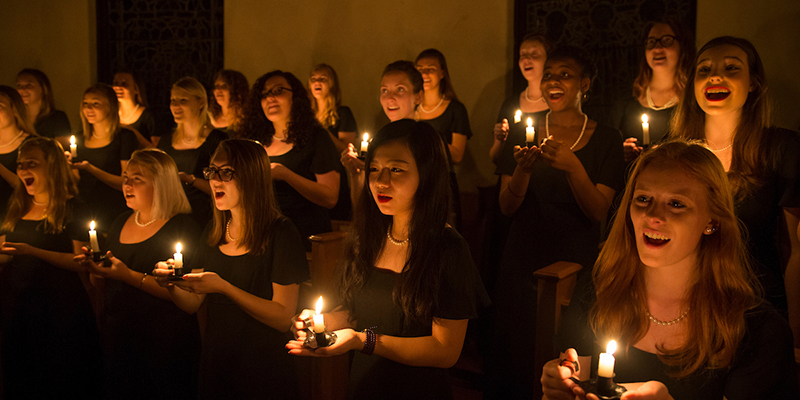 Members of the Choraliers hold candles and sing in a darkened chapel during the annual Ceremony of Carols performance, 2016