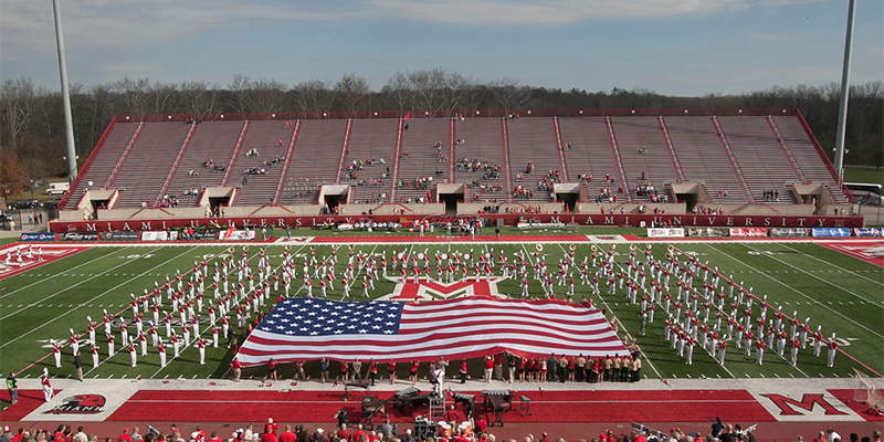 The marching band takes the field as a large American flag is displayed