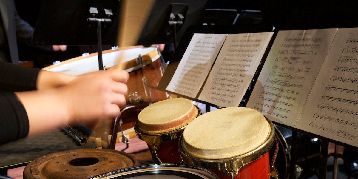 With music on a stand, hands holding sticks are striking drums in a kit that includes world percussion instruments at a concert
