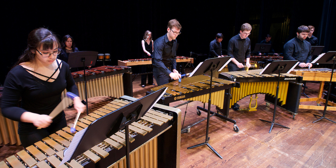 Members of the Percussion Ensemble perform on marimbas onstage at Hall Auditorium