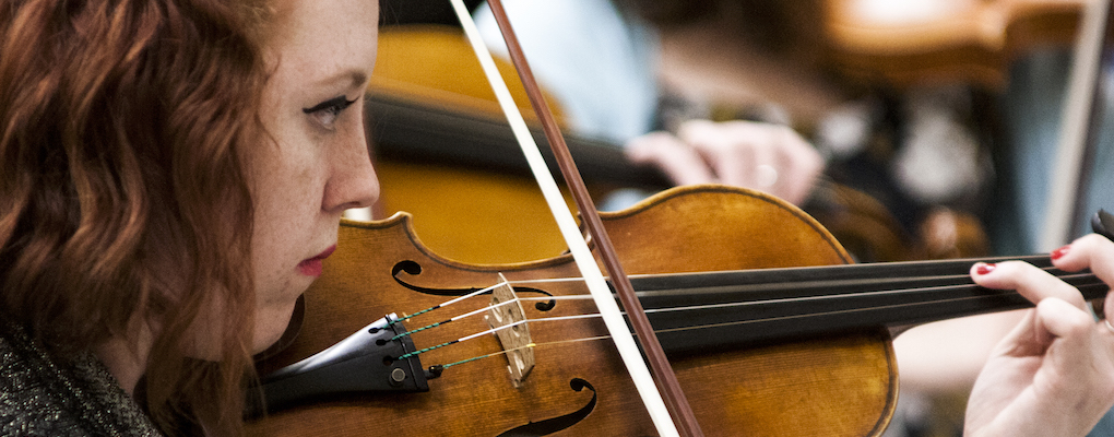 A closeup of a violinist during Morpheus chamber orchestra rehearsal