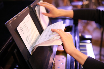 A person sorts through music in a folder on a piano ledge.