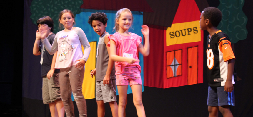 Group of children rehearsing a play onstage