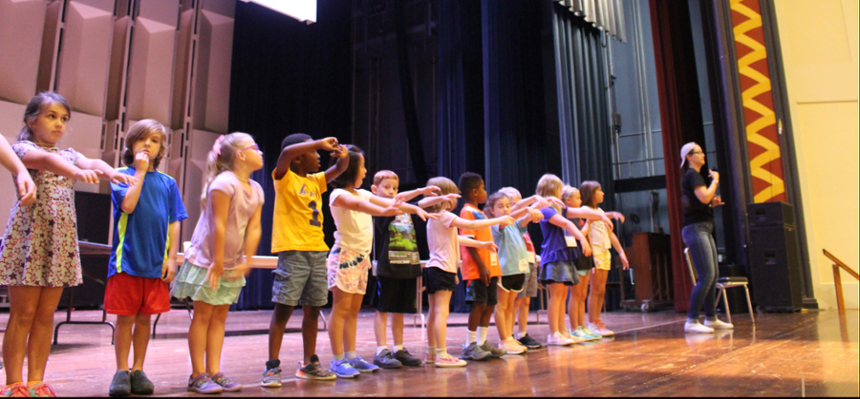 A row of children across the front of the stage, with an adult facilitator