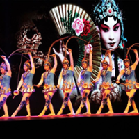 A row of colorfully dressed performers perform tricks while a woman with fan is projected on the background
