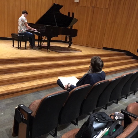 Seen from behind, David Fray takes notes from the audience as a piano student performs onstage at Souers Recital Hall