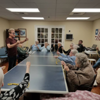 Residents of Knolls of Oxford each hold a length of rope, seated around a large table as Kevin Spencer teaches a magic trick