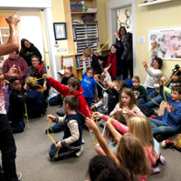 Children at McGuffey Montessori sit on the floor and hold lengths of rope out as Kevin Spencer teaches a magic trick