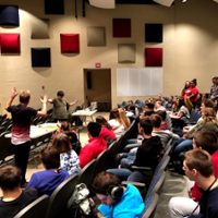 With raised arms, Kevin Spencer works with Best Buddies group at Talawanda High School