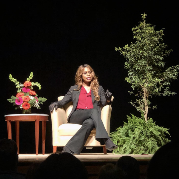Laverne Cox sits in an easy chair onstage, flanked by plants and a small table