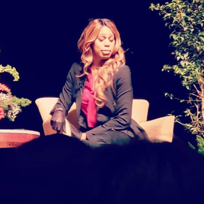 Laverne Cox onstage looks to her side