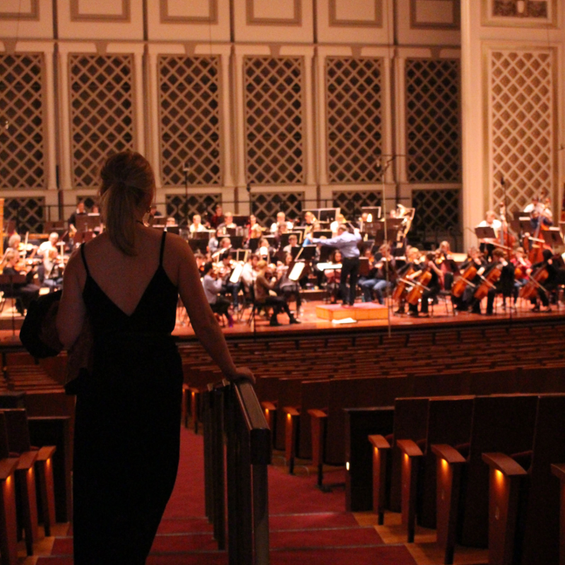 A woman stands in the aisle and faces the stage as the orchestra rehearses