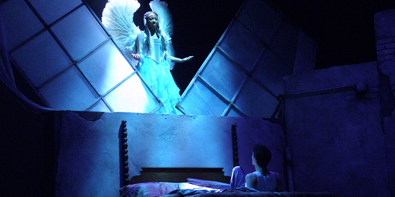 An angel hovers over a person in bed in Angels in America