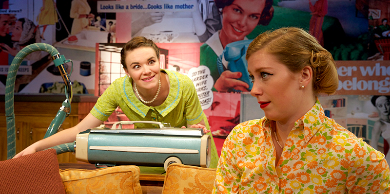 A excited woman leans over a canister vacuum cleaner behind another woman, who is seated on a couch, in a scene from Bliss, or Emily Post is Dead