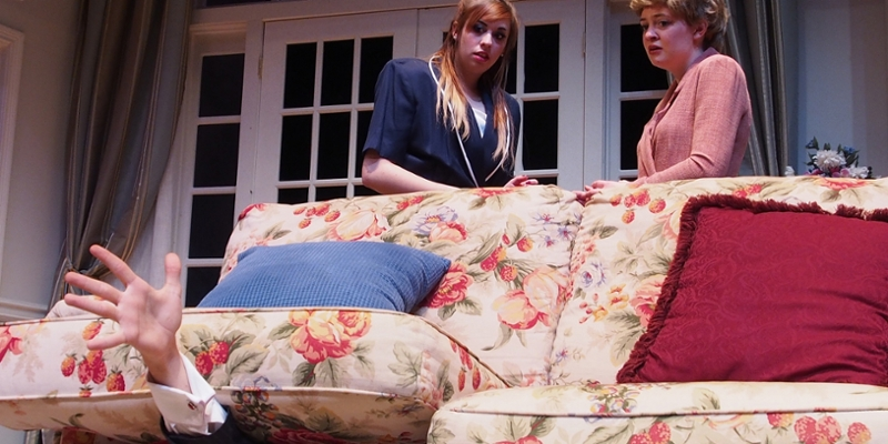 A hand reaches from beneath the couch cushions as two women look on in a scene from Communicating Doors