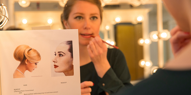 A student sits at a mirror and applies makeup by referring to a design