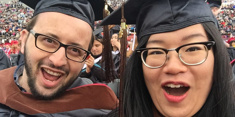 Two graduates in academic regalia mugging for the camera in a close-up view