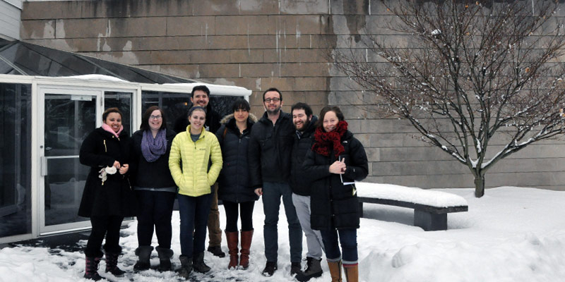 Students and visiting designer wearing winter coats standing outside a museum in the snow