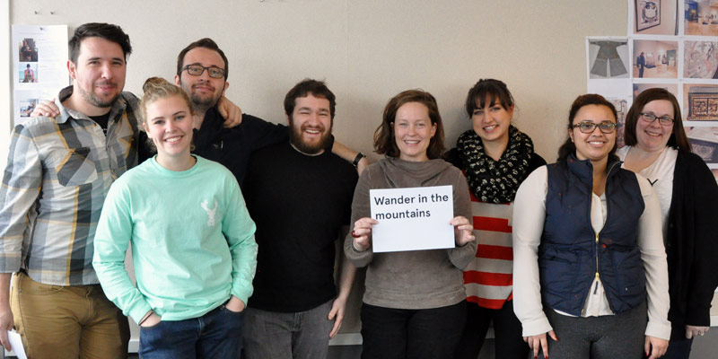Students and a visiting designer posing together. A woman holds a sign reading ' Wander in the mountains'