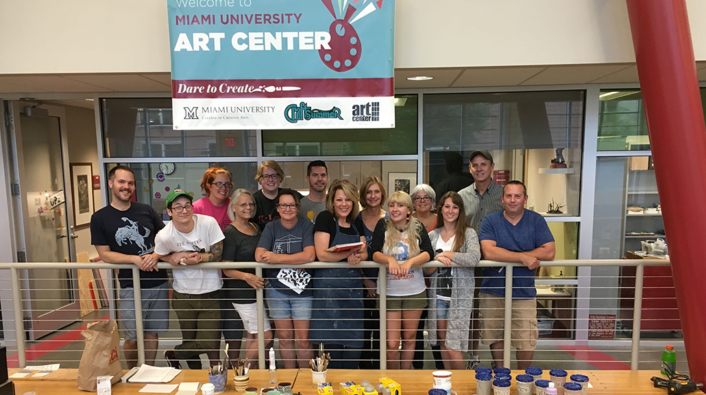 A group of students pose by the railing of the Art Center beneath a Welcome sign. Art supplies are visible on a table below them.