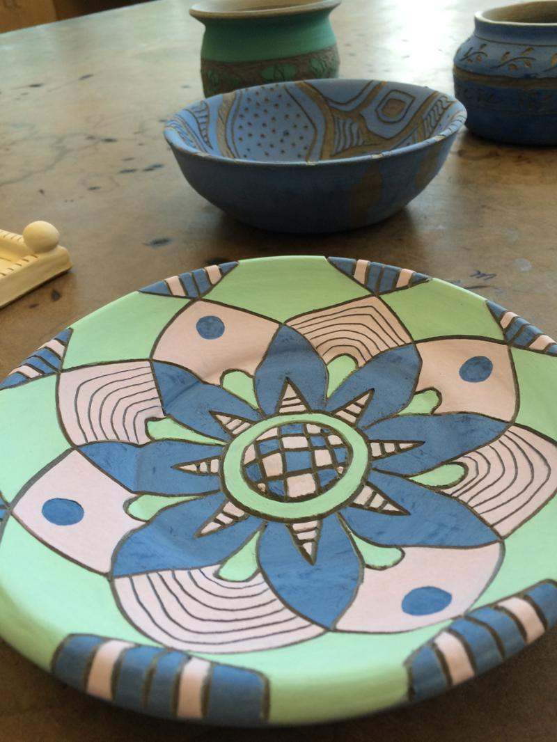 In foreground, a colorful patterned plate. Other pieces in background.