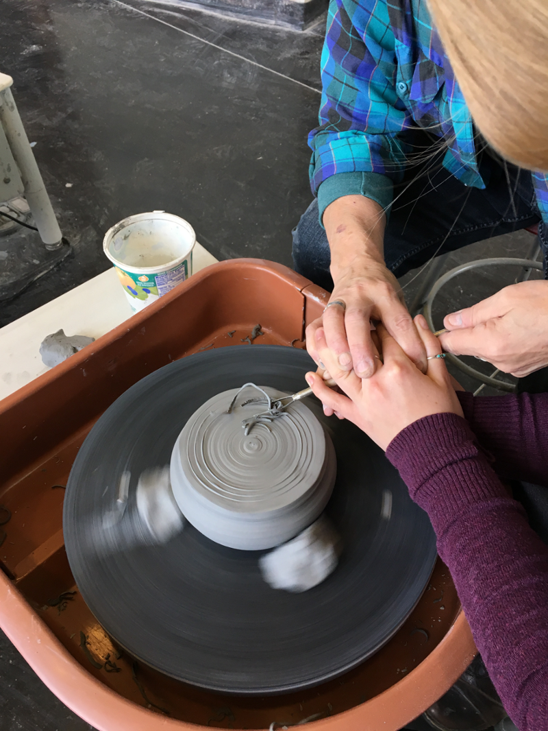 Student and instructor use tools to carve a project on the pottery wheel