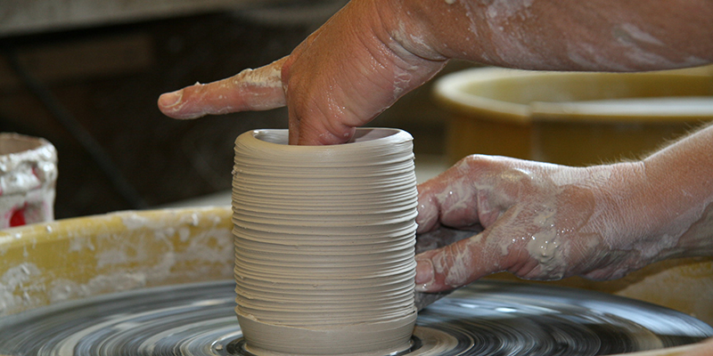 An artist shapes a piece of pottery on the pottery wheel
