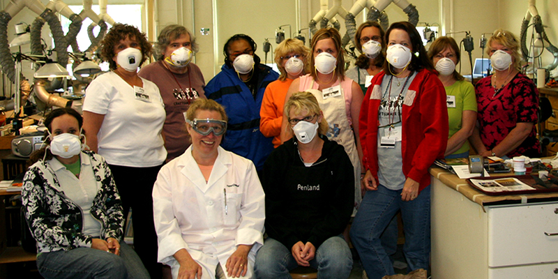 A group of Enameling students poses with protective masks on their faces
