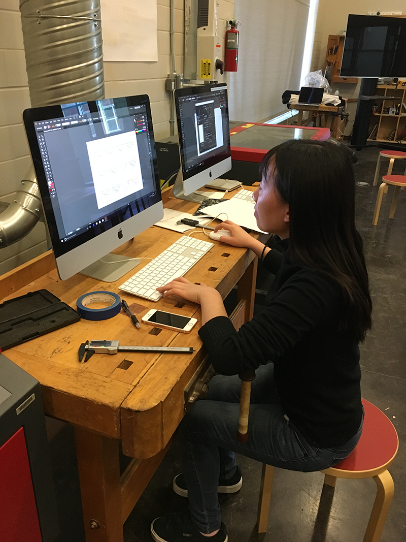 A student works at a computer on a digital design project.