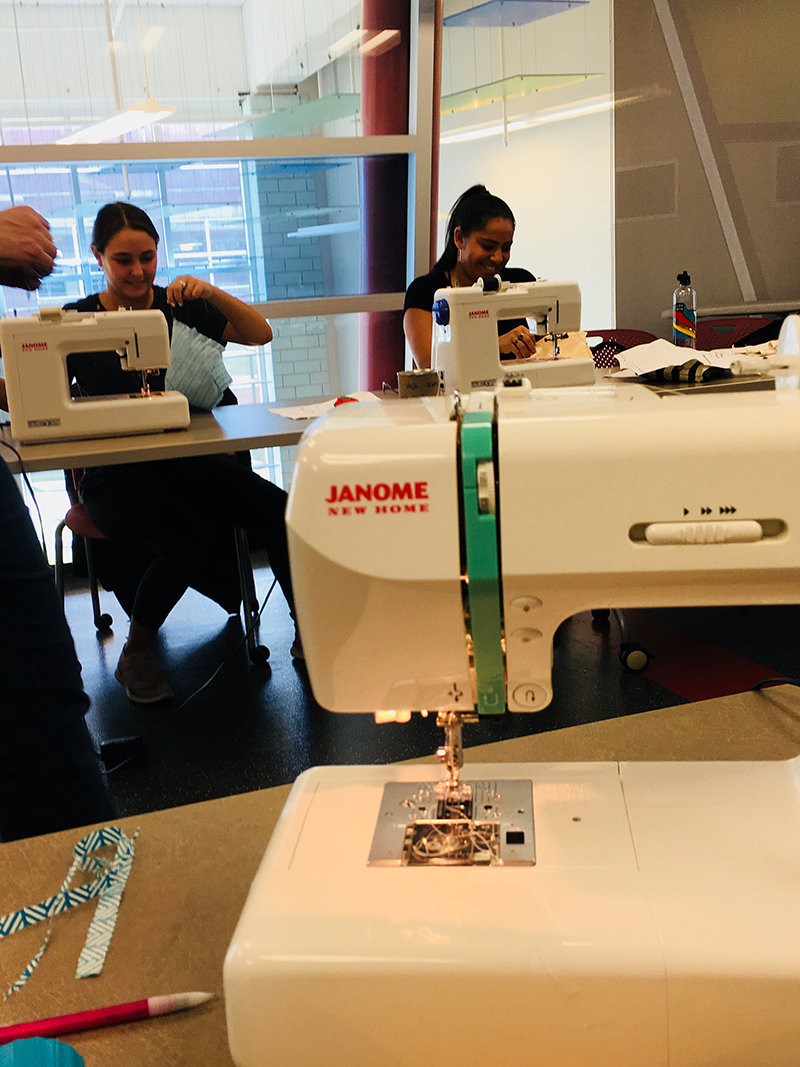 Closeup of a sewing machine, as students work in background