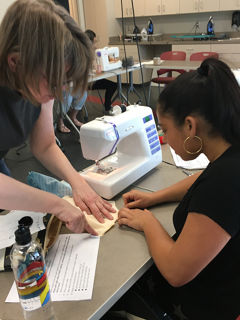 Sewing teacher assists student with a project