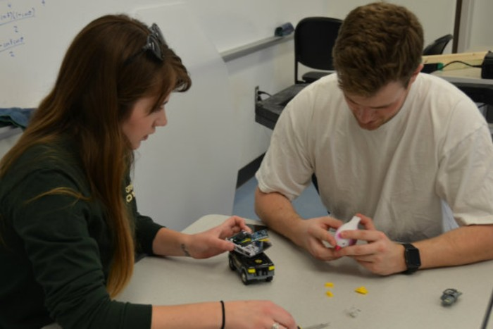 Two students working with a toy bird and truck